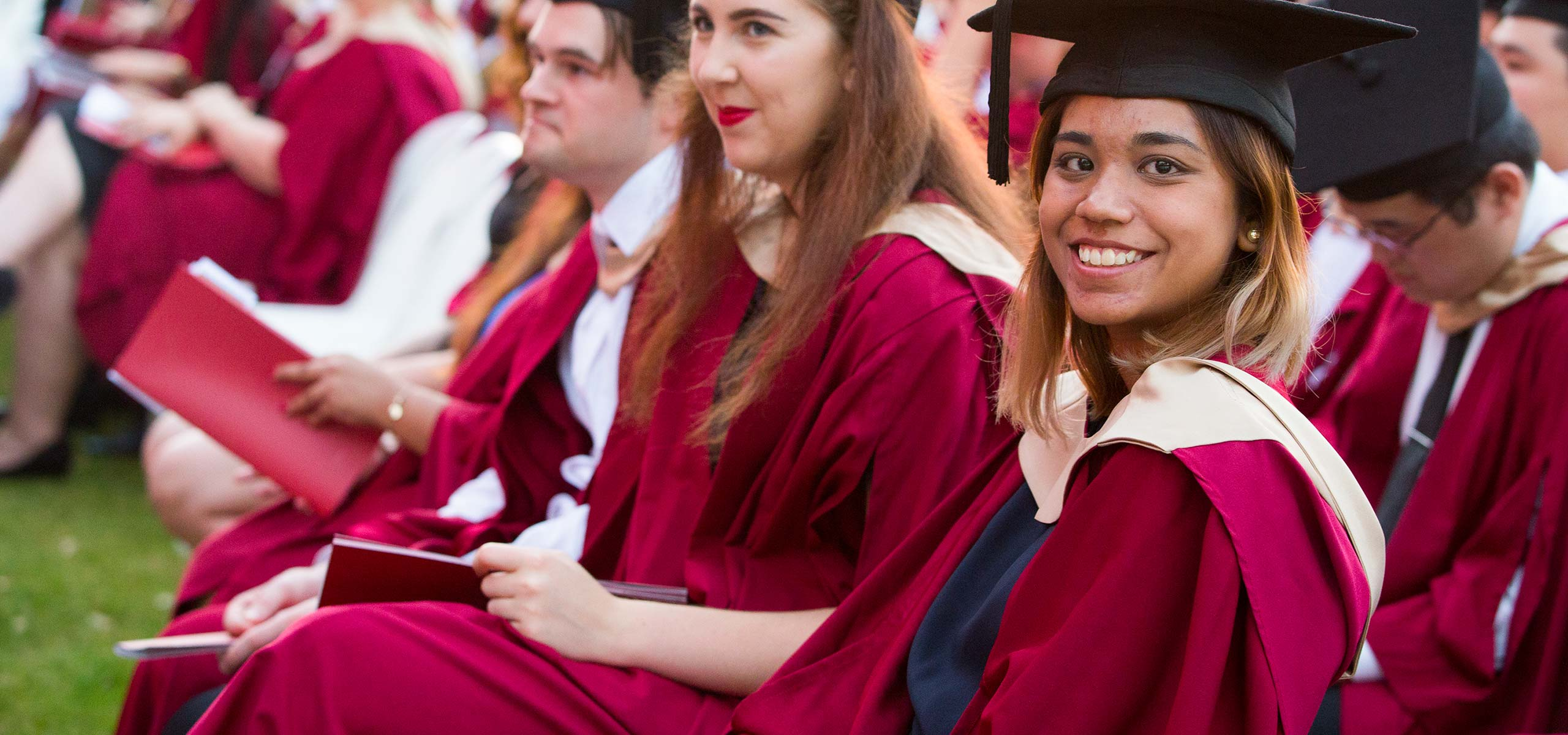 Female graduate in gown, smiling at camera