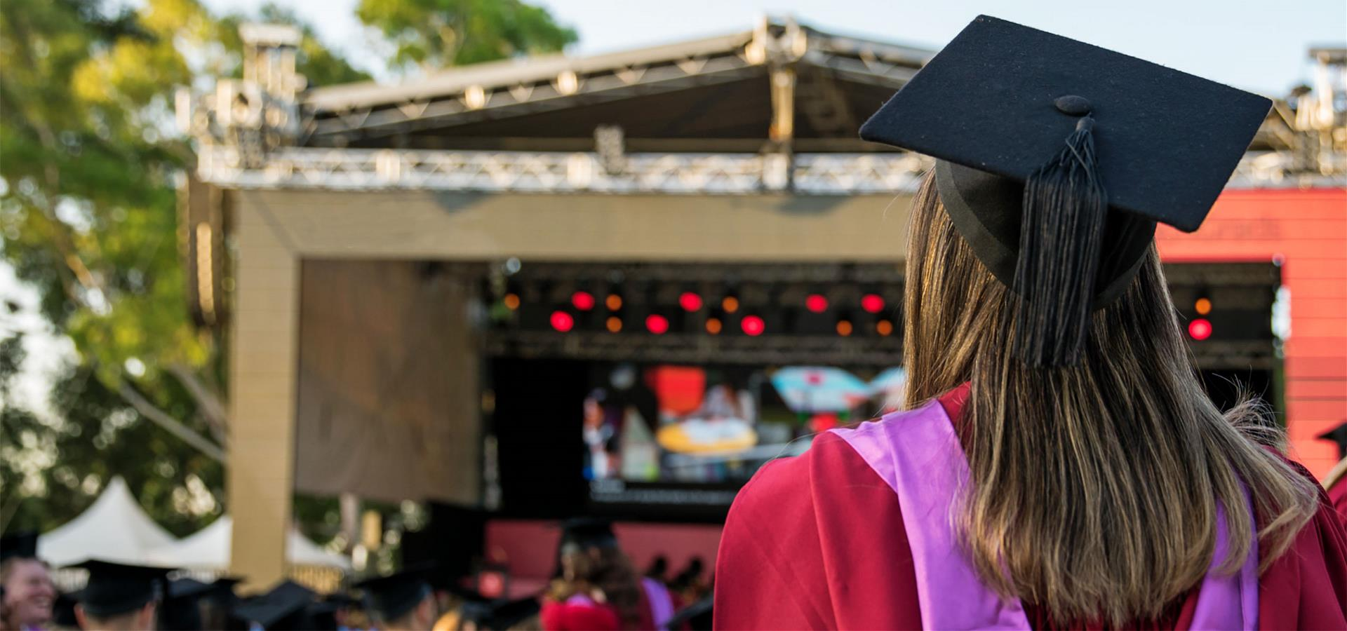 Murdoch student wearing regalia and cap walking to their graduation ceremony