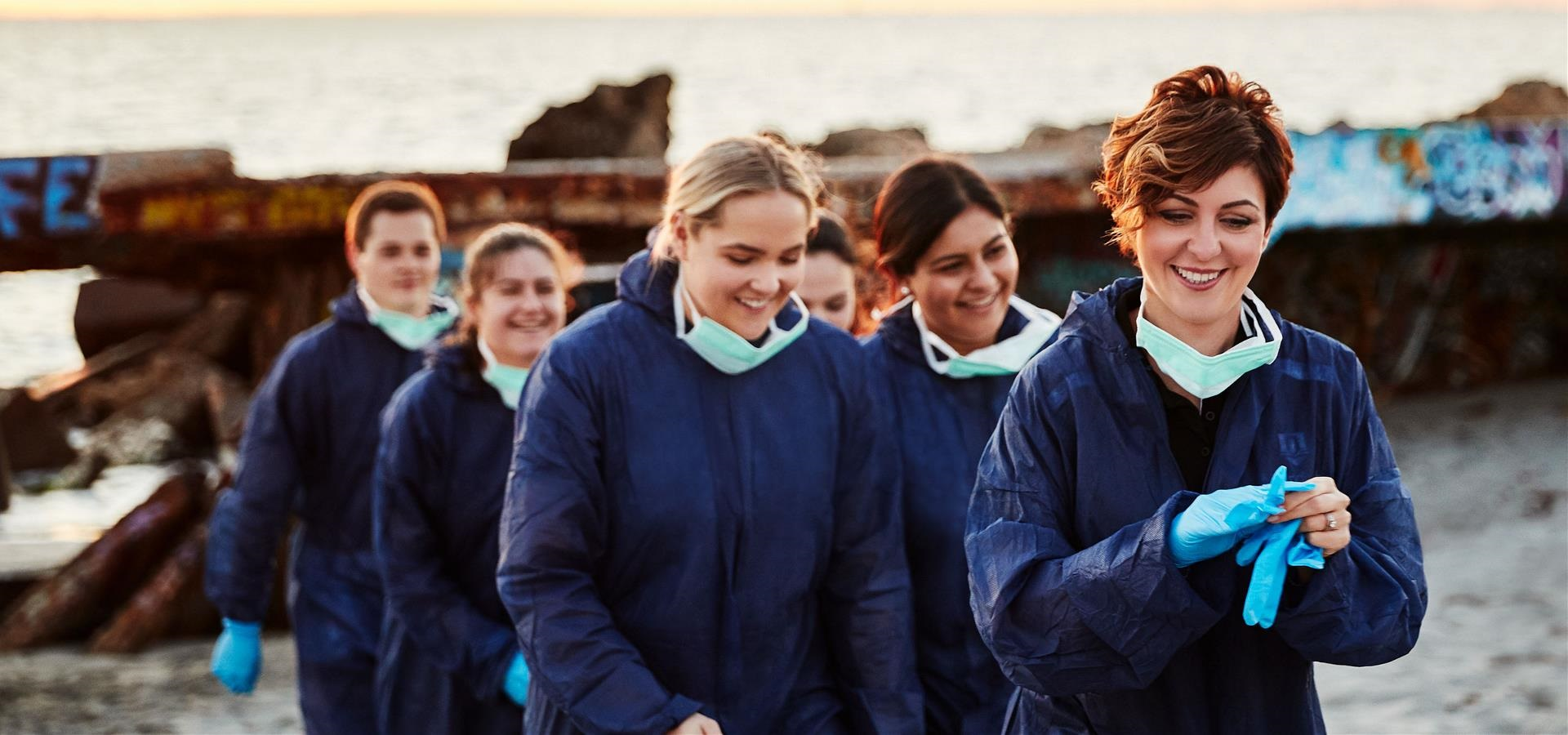 Paola Magni and her students wearing blue hazard suit