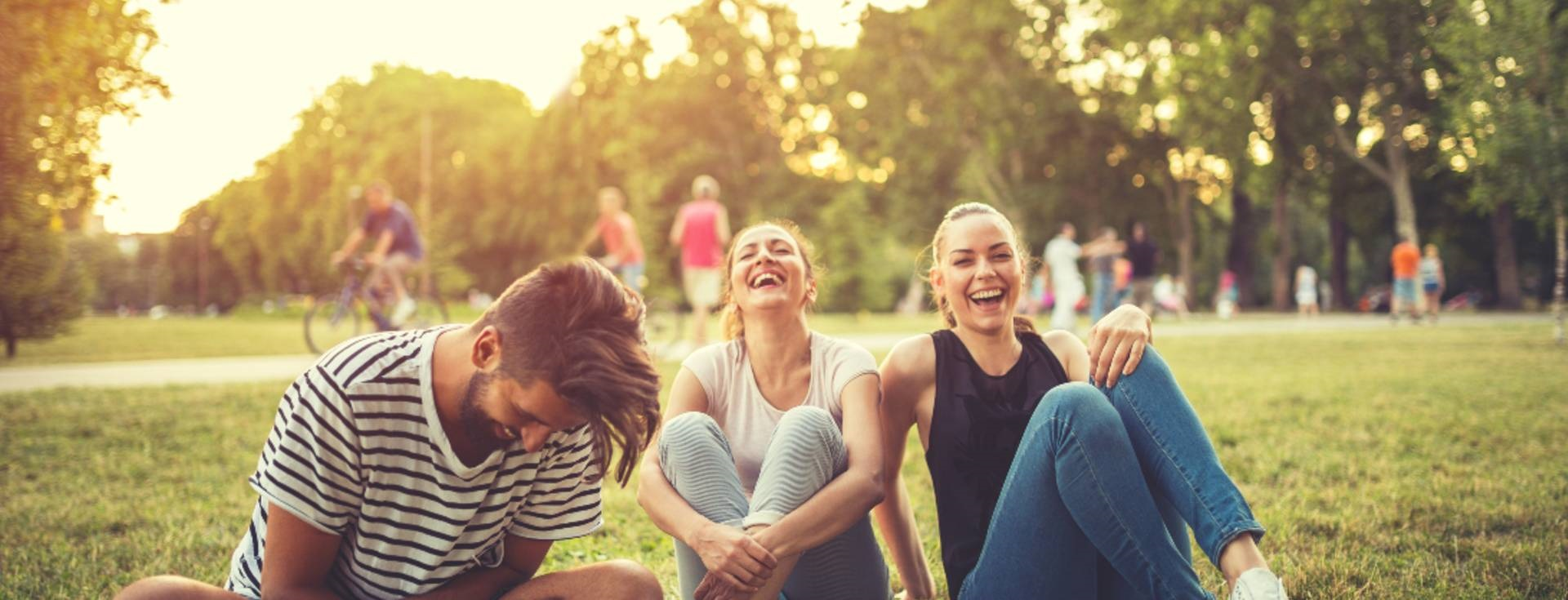 Three friends sitting on the grass laughing happily.