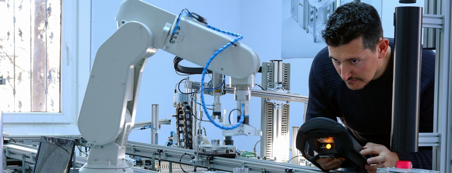 Man programming a robotic arm in a lab.