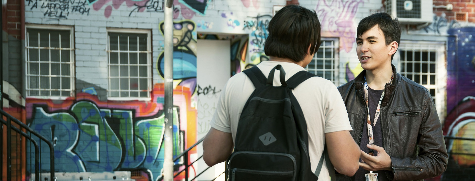 Two students having a discussion in a graffiti alleyway