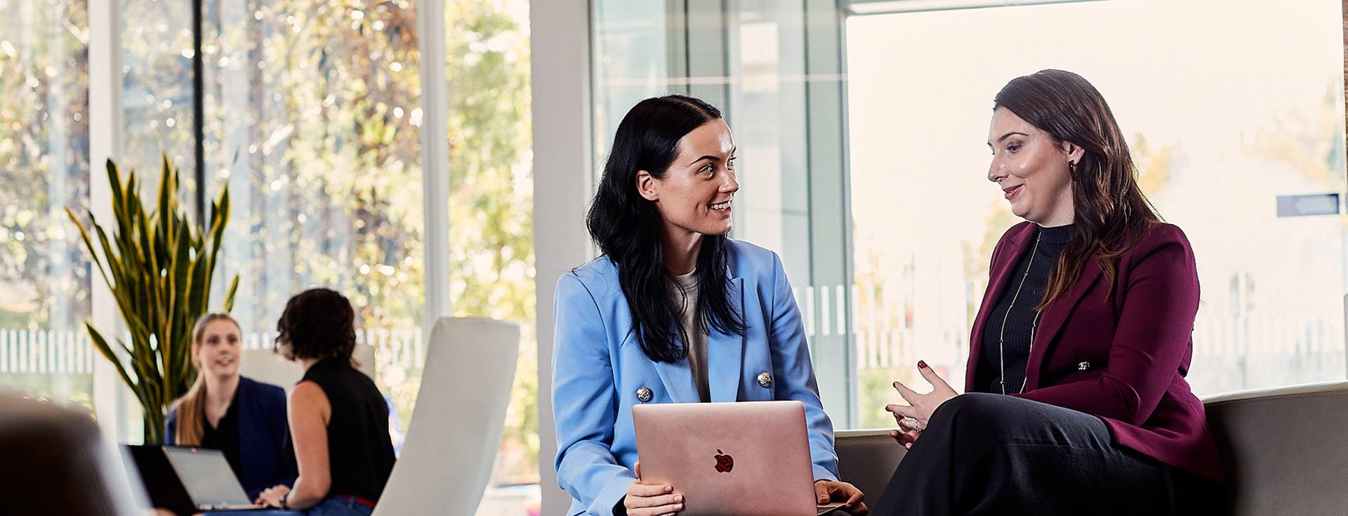 Two business women talking over a laptop