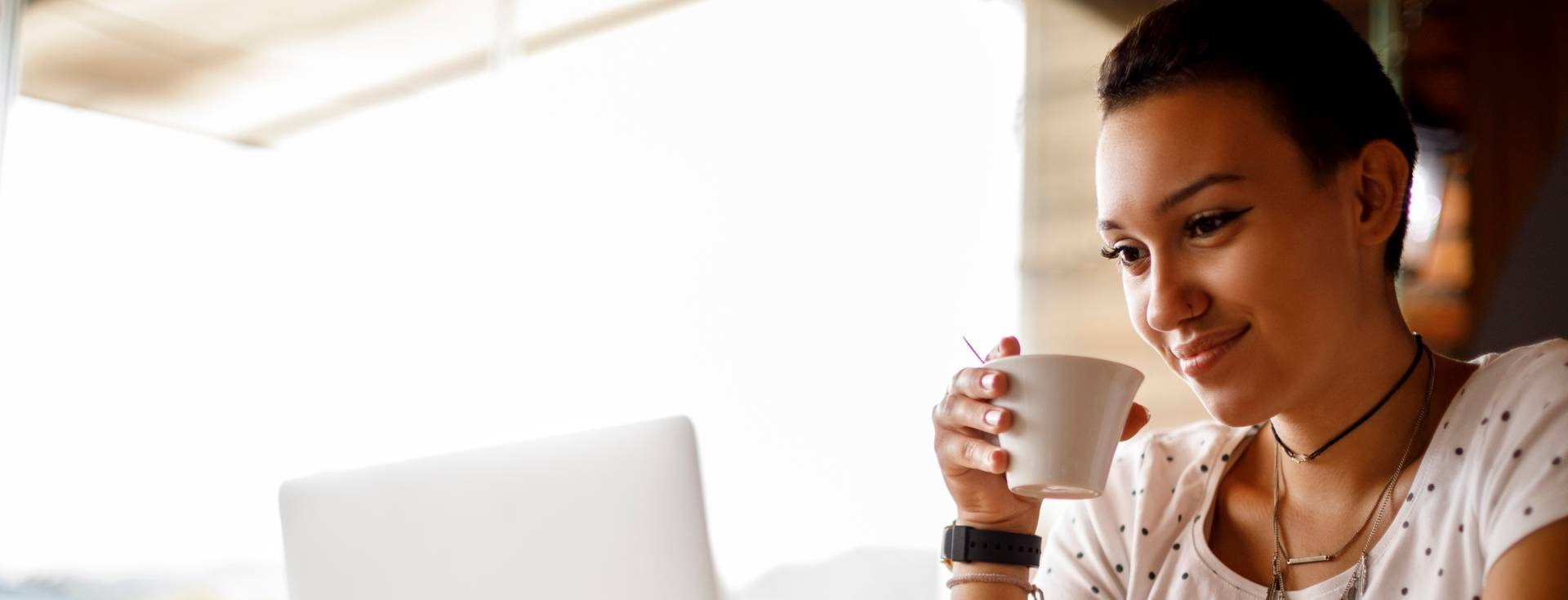 Woman smiling while at a computer with a coffee.