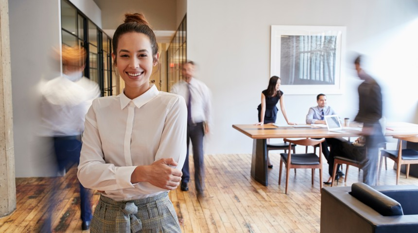 Professional woman smiling in a busy office
