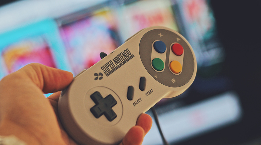 Hand holding 90s gaming console