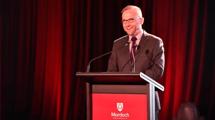 Adam Bandt in brown suit giving a speech on a Murdoch University podium