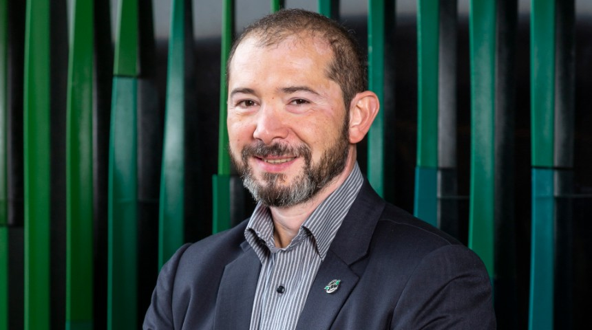 Aleks Nikoloski standing in front of a green wall