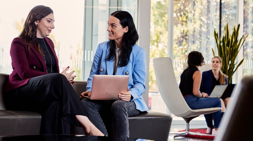 Two women sitting on a couch with a laptop having a business meeting