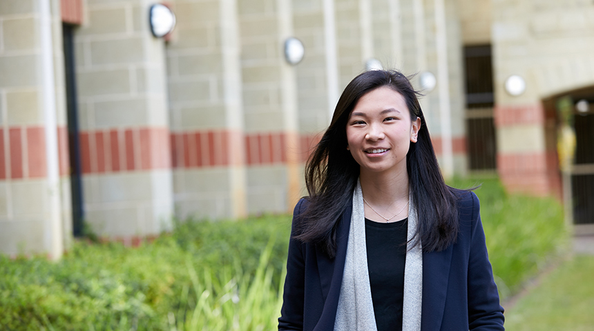 International student Andra Julinar smiling and posing in front of building at Murdoch Perth campus