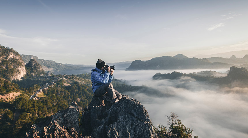 Man taking a photo at the top of a misty mountain range