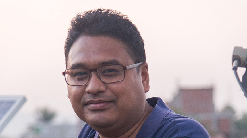 Murdoch alumnus Avishek Malla smiling at camera with solar panel in background