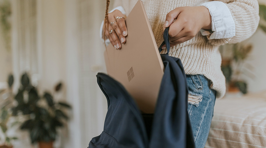 Woman putting laptop in bag