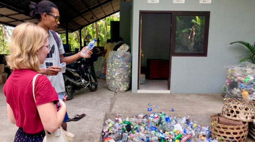 people looking at empty plastic bottles for recycling