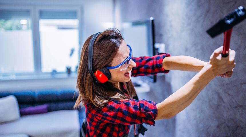 Woman smashing wall with tool
