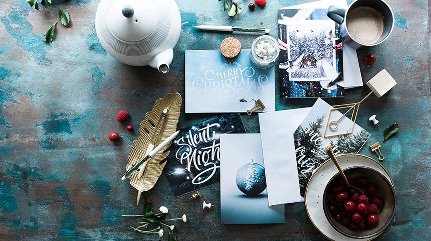 Overlay of Christmas arts and crafts spread over a table