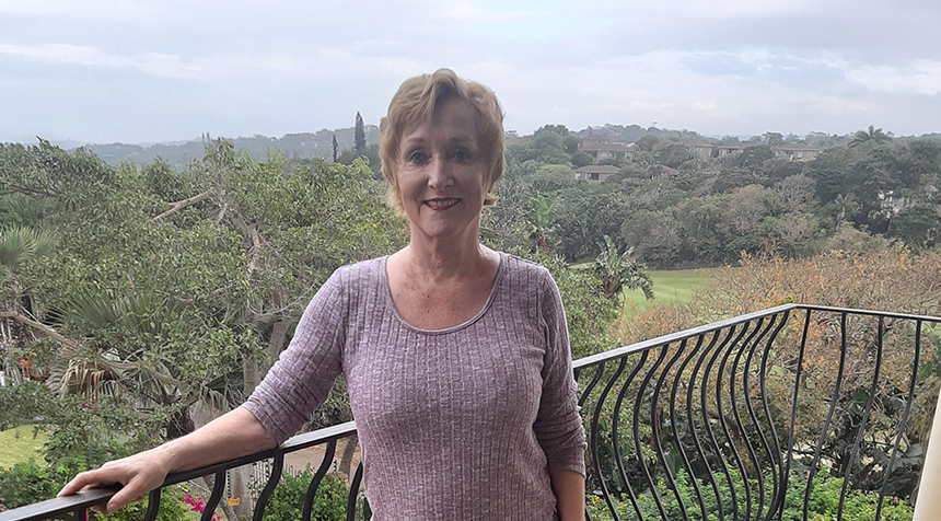 Cynthia stands on her balcony overlooking the South African jungle