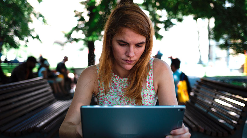 Girl researching on her laptop in a park