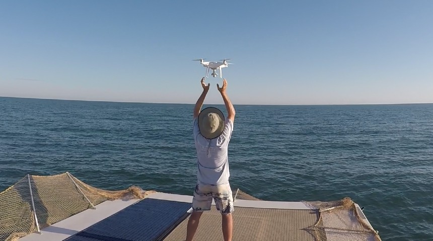 man launching drone off a boat