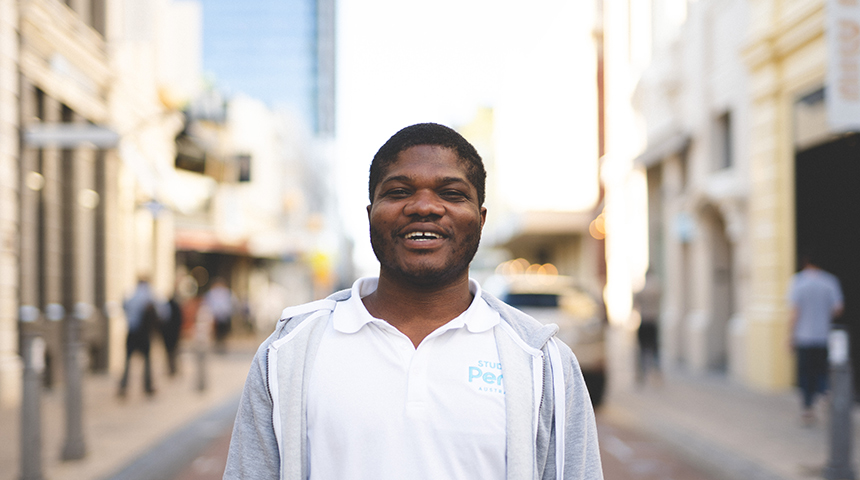 International student Emmanuel Dei standing and smiling on King Street, Perth