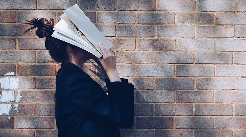 Girl holding book to face
