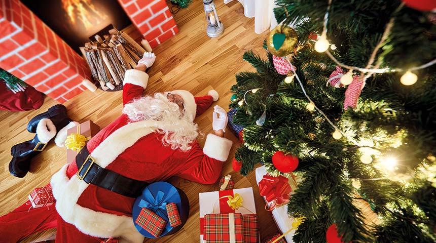 Stressed Santa lying among presents