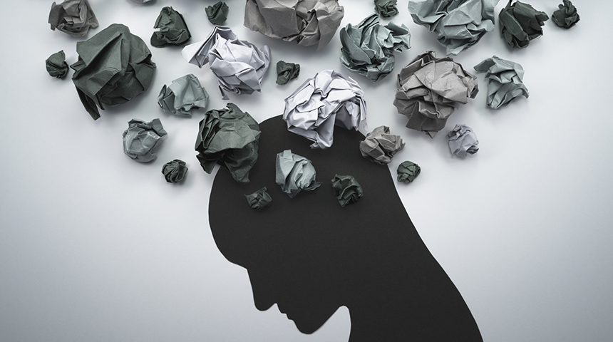 Silhouette of head looking down with scrunched up paper resembling thoughts