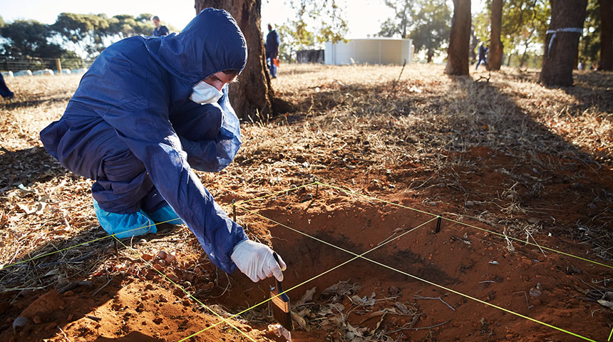 forensic student dusting evidence in sand