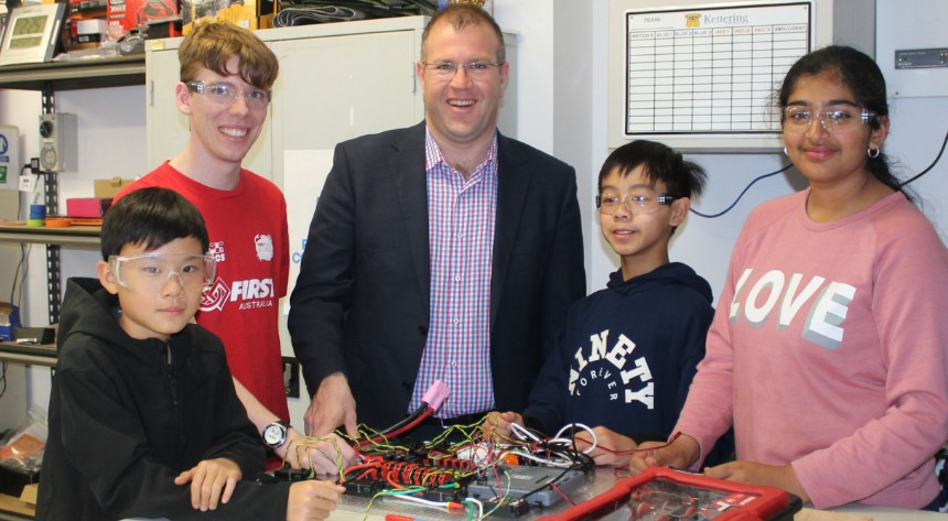 Students with Ben Morton building a robot at a table