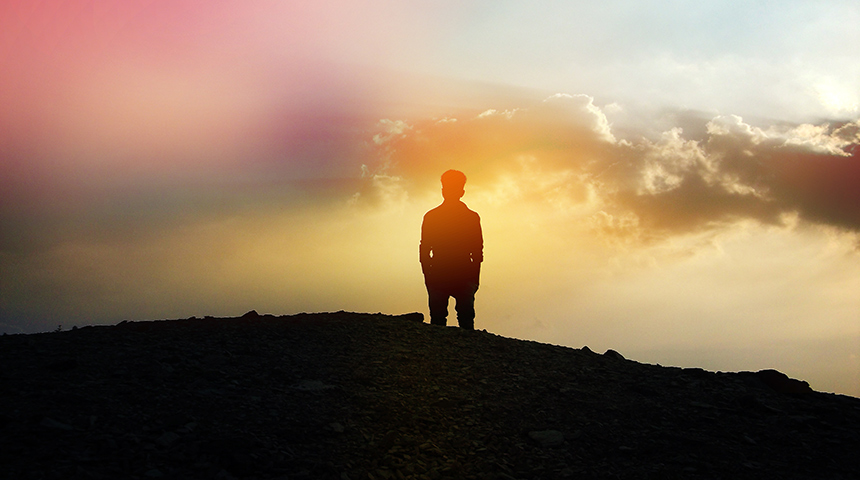 Silhouette of person standing on a hill