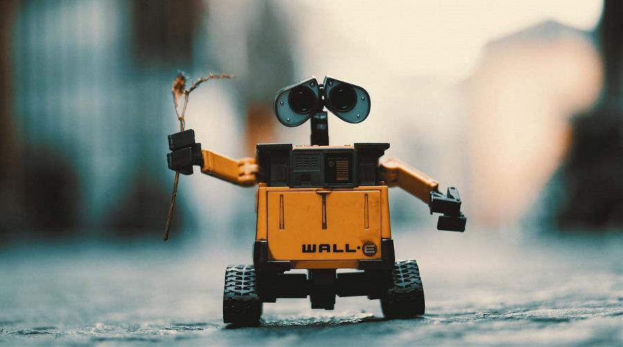 Toy robot holds up twig in his hands