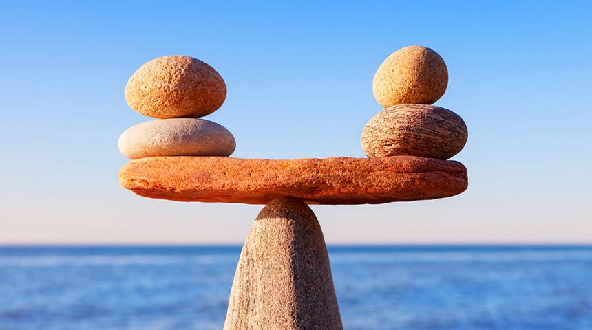 Pebbles balancing against an ocean backdrop