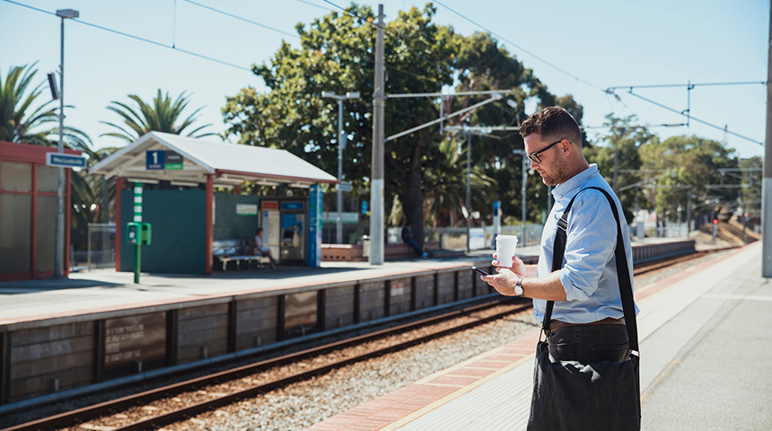 Man with a bag and coffee waiting at a Perth train station