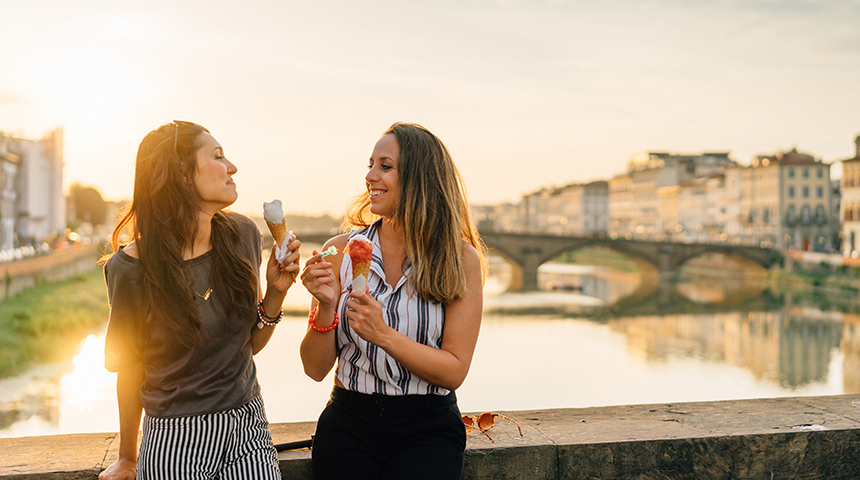 Two young women eating ice cream on bridge in italy