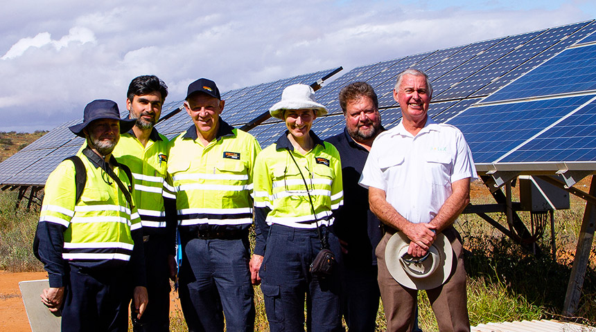 Group of people standing together with solar panels in the background
