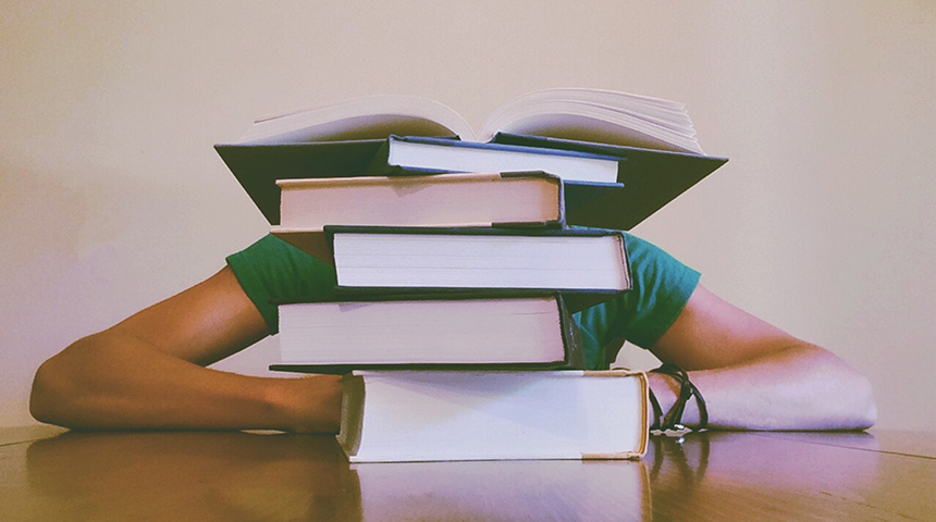 Student with head on hands behind pile of textbooks