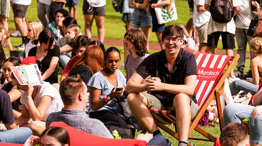 Image of student sitting on deckchair on Bush Court, smiling to a friend