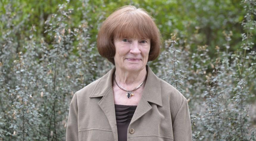 Janet Bornman smiling next to bushes