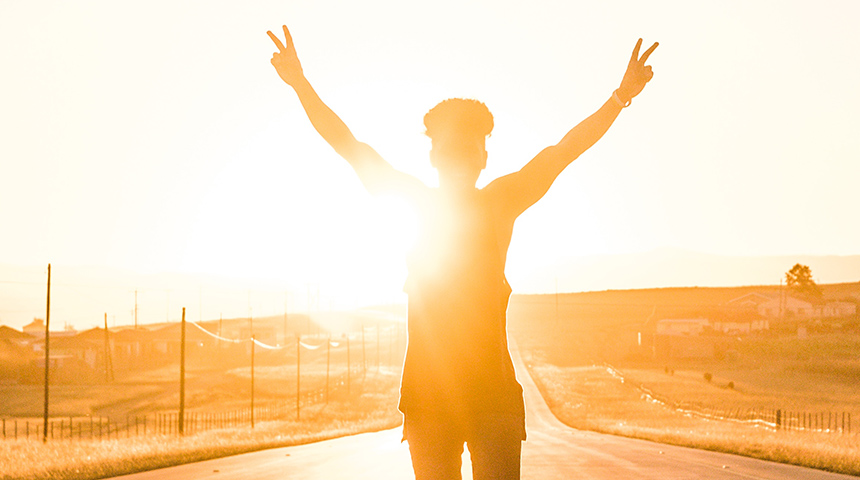 Boy standing on the road with his hands in the air and the sun setting behind him