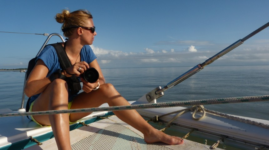 Blonde girl on left hand side of a sailing boat looking at the ocean and holding a camera.
