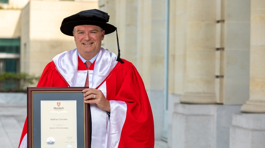 Dr Mathias Cormann holding his Honourary Doctorate
