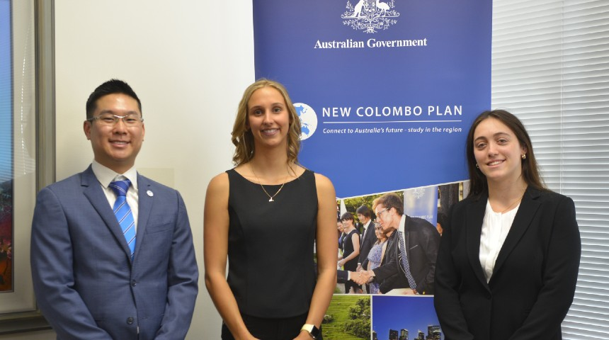 Three Murdoch students, recipients of the New Colombo Plan (NCP) Scholarship, stand in front of NCP banner
