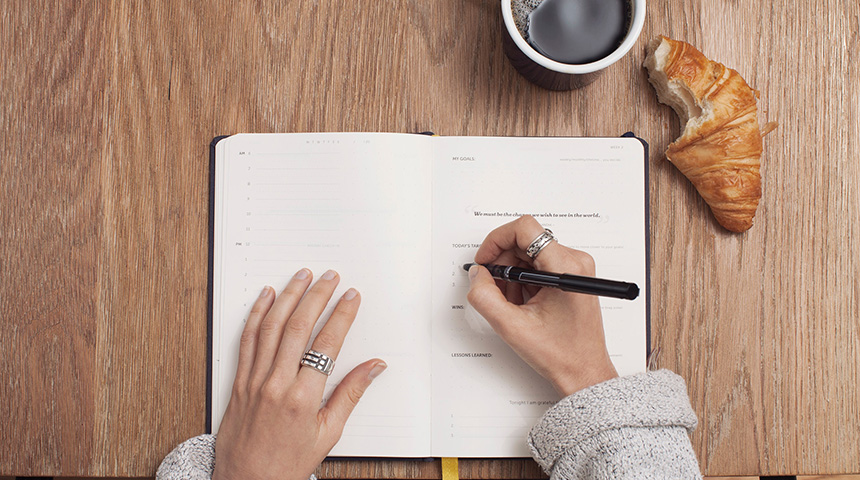 Top view of person writing in diary at desk