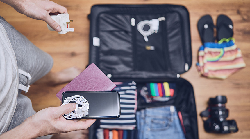 Man standing over suitcase filled with clothes holding a phone, passport, and adaptor