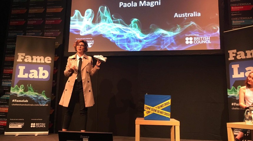 Paola Magni holding a shoe performing at the International FameLab finals 2019