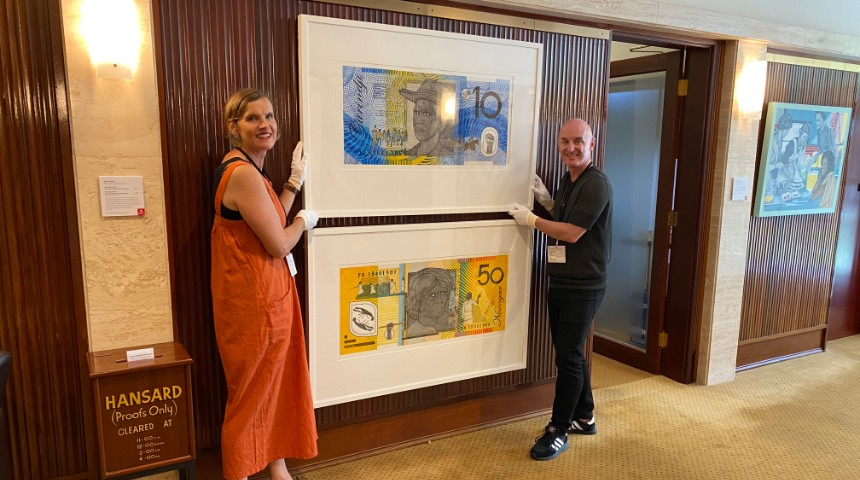Murdoch curators Mark Stewart & Jane Chambers installing artworks resembling money by Ryan Presley