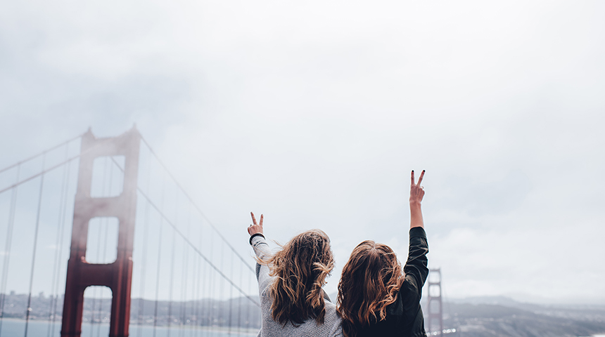 Two girls waving their hand in the air in front of bridge