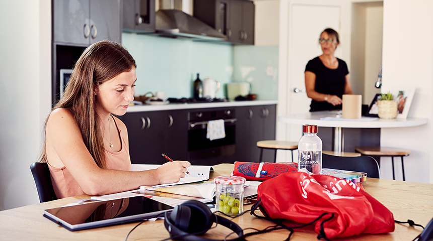 Female student sitting at kitchen table with mum in the background