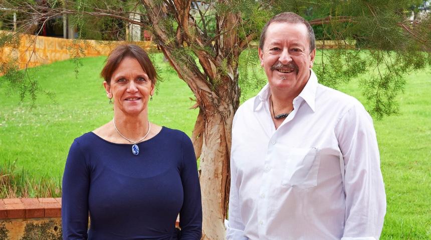 Professor Sue Fletcher and Professor Steve Wilton under a tree smiling at camera
