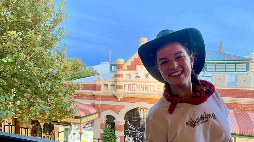 Young woman in cowboy hat and white t-shirt smiling and posing outside of Fremantle Markets